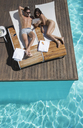 Couple relaxing on lounge chairs at poolside - CAIF07734