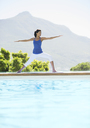 Woman practicing yoga at poolside - CAIF07737