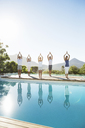 People practicing yoga at poolside - CAIF07740