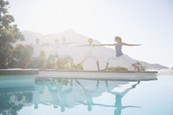 People practicing yoga at poolside - CAIF07749