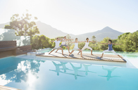 People practicing yoga at poolside - CAIF07752