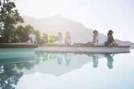 People practicing yoga at poolside - CAIF07755
