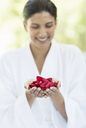 Woman holding handful of flower petals - CAIF07764