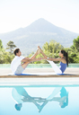 Couple practicing yoga poolside - CAIF07773