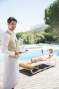 Waiter serving woman at poolside - CAIF07800