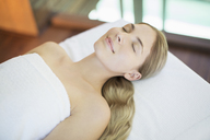 Smiling woman relaxing on massage table in spa - CAIF07824