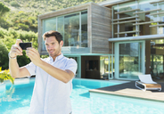 Man taking self-portrait with camera phone at poolside - CAIF07845