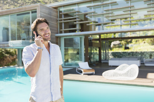 Man talking on cell phone at poolside - CAIF07854