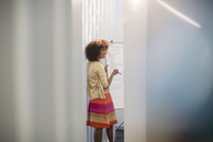 Businesswoman at whiteboard in conference room - CAIF07863