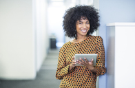 Portrait of woman using digital tablet in office - CAIF07884