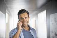 Businessman talking on cell phone in corridor - CAIF07908