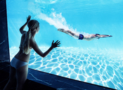 Woman watching boyfriend underwater in swimming pool - CAIF07926