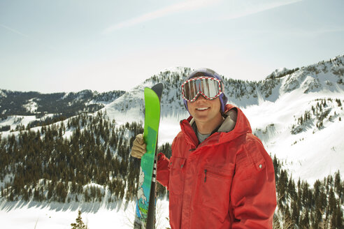 Portrait of man wearing ski goggles standing on snow covered mountain - CAVF01397