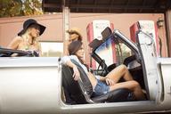 Friends sitting in car at fuel pump - CAVF01433