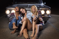 Happy friends sitting against convertible car - CAVF01442