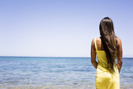 Rear view of woman standing at shore against sea - CAVF01454