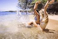 Friends splashing water while sitting at shore - CAVF01463