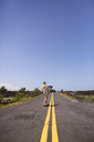 Woman carrying surfboard while skateboarding on road against blue sky - CAVF01484