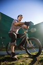 Low angle view of man sitting on bicycle against sky - CAVF01499