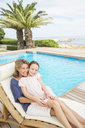 Grandmother and granddaughter relaxing at poolside - CAIF07928