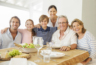 Multi-generation family smiling together at table - CAIF07937