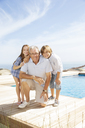 Grandfather and grandchildren smiling at poolside - CAIF07940
