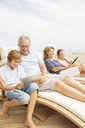 Grandparents and grandchildren using digital tablets at poolside - CAIF07943