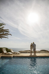 Older couple hugging by pool - CAIF07949