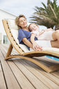 Older woman and granddaughter relaxing in lawn chair - CAIF07958