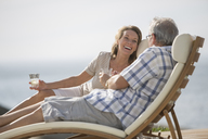 Older couple relaxing in lawn chairs - CAIF07961