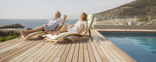 Older couple relaxing in lawn chairs by pool - CAIF07964