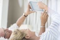 Older couple using digital tablet on bed - CAIF07970