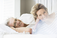 Older couple smiling on bed - CAIF07973