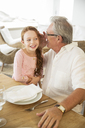 Older man and granddaughter whispering at table - CAIF07979