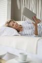 Older woman using digital tablet on bed - CAIF07994