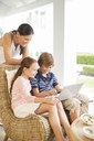 Mother and children using laptop in living room - CAIF07997