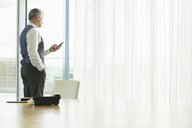 Businessman using cell phone in office - CAIF08009