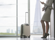 Businesswoman with suitcase in airport - CAIF08012