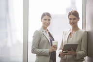 Businesswomen smiling in office - CAIF08015