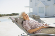 Senior woman sleeping on lounge chair at poolside - CAIF08054