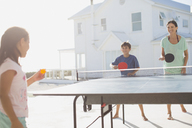 Family playing table tennis together outside house - CAIF08057
