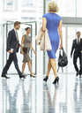 Business people walking in office lobby - CAIF08084