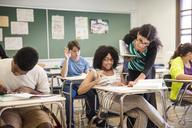 Teacher guiding woman while teaching in classroom - CAVF01538