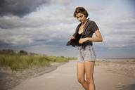 Woman holding jacket while standing on road against sky - CAVF01562