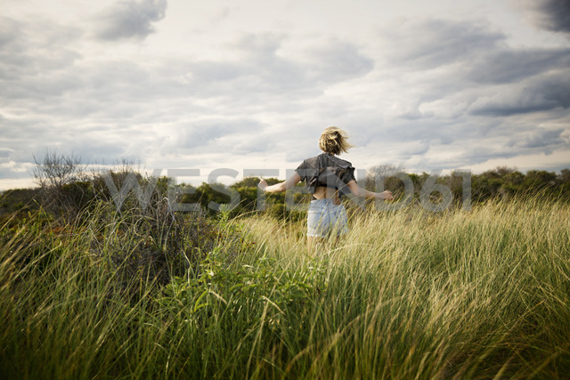 Rear view of woman running on grassy field against cloudy sky - CAVF01565