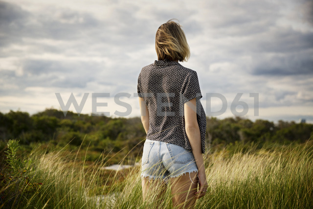 Rear view of woman standing on grassy field against cloudy sky - CAVF01568