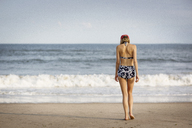 Rear view of woman walking on shore at beach - CAVF01571