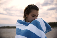 Woman with eyes closed wrapped in towel standing against sky - CAVF01583