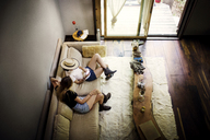 High angle view of friends using mobile phone while sitting on sofa at home - CAVF01649