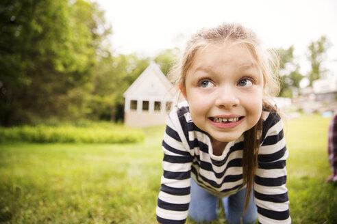 Girl looking away while kneeling on field in backyard - CAVF01685